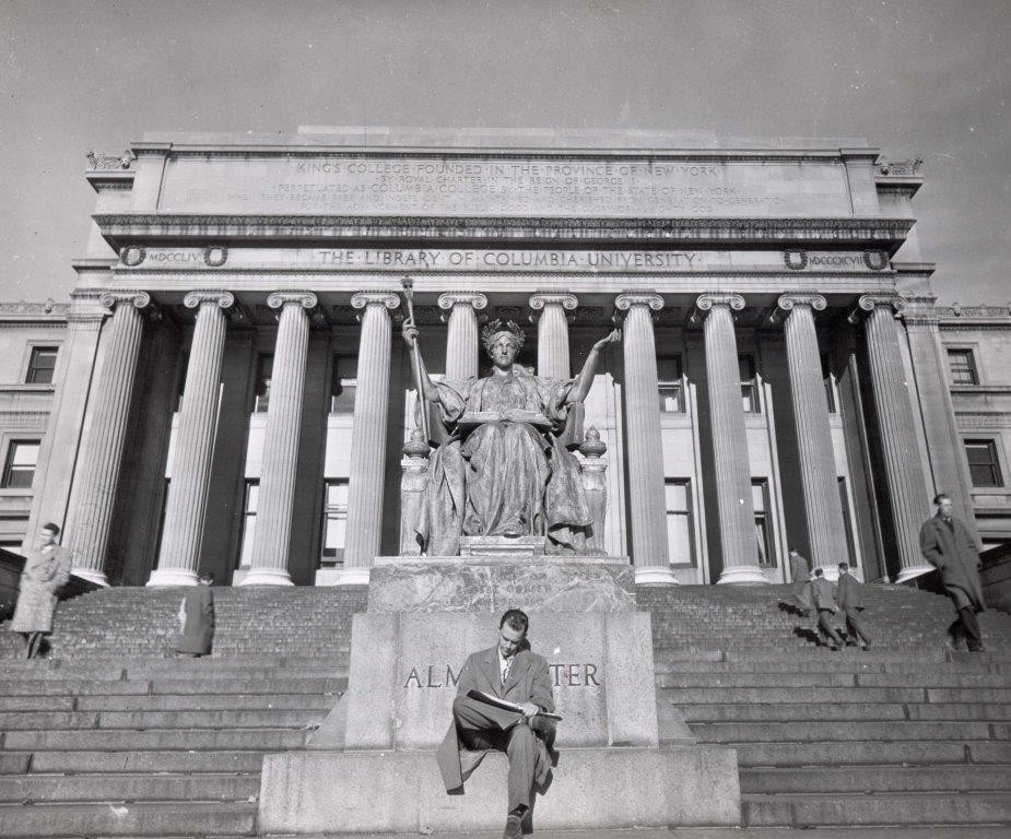 Man sitting in front of Alma Mater statue.