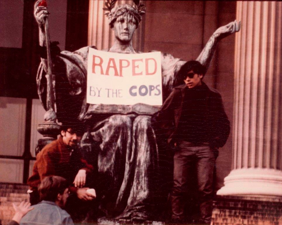 "Alma Mater statue with two young men posing in front of her with a sign on her lap saying ""Raped By The Cops."""
