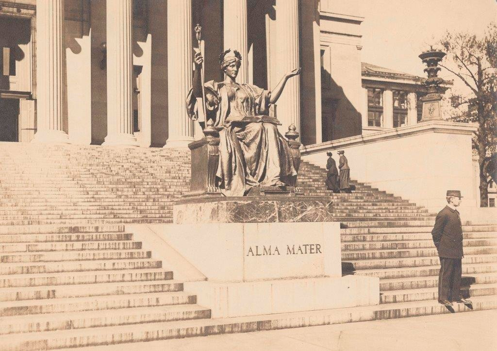View of Alma Mater in gold leaf with guard standing at her base and two women walking up the stairs to Low Library.